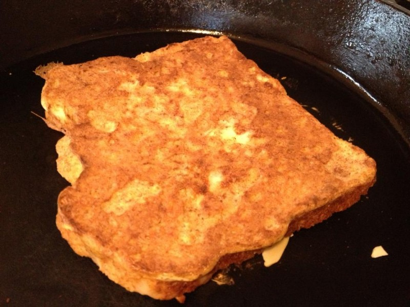french toast cooking in pan with almonds on top