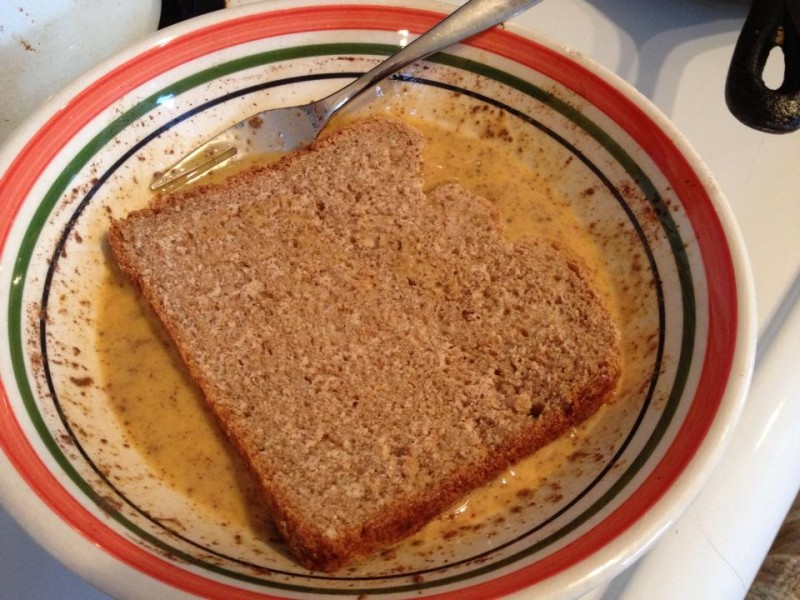 bread soaking in batter for almond french toast